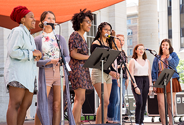 Young women on an outdoor stage singing