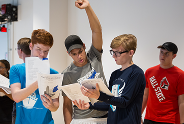 Students looking at scripts